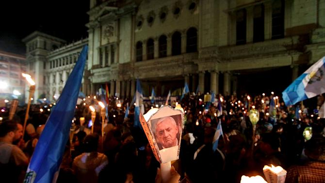 Demonstrator holds up a candle with a picture of Guatemala's President Otto Perez Molina, during a protest demanding his resignation in Guatemala City