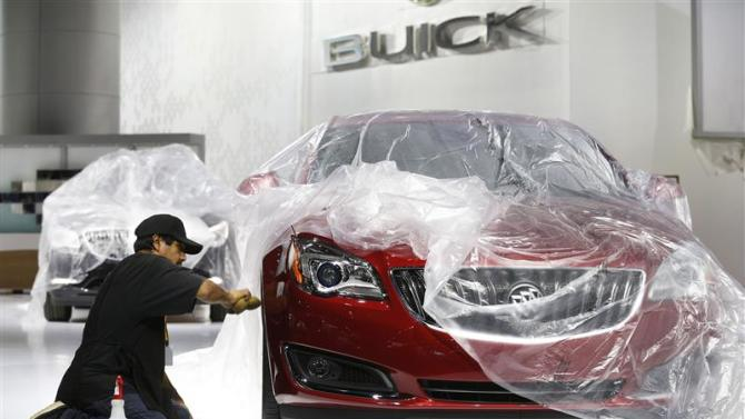 A worker details a General Motors 2014 Buick Regal vehicle under wraps, as they prepare the displays for the media preview of the North American International Auto Show in Detroit