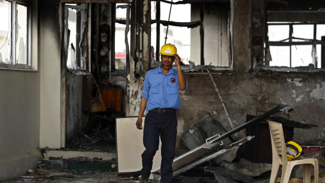 A security guard stands near a burnt down structure of Maruti Suzuki factory in Manesar, near New Delhi, India, Thursday, July 19, 2012. According to news reports, one person died and at least 40 people were injured in Wednesday's labor unrest at the Manesar facility of India's largest passenger car maker. (AP Photo/ Saurabh Das)