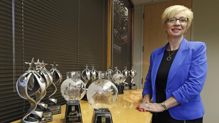 """In this Friday, June 15, 2012 photo, Kathy Miller, president of Total Event Resources, poses for a photograph next to trophies awarded to her company in her offices in Schaumburg, Ill. In 2008, her events planning company was having its best year ever. She and her husband had set aside money to put their two sons through college, with enough left in savings for """"a very nice life"""" in the Chicago suburb. Then the financial crisis sent the stock market tumbling and the corporate customers who had kept Miller's company busy, stopped calling. When the government reported that the Great Recession claimed nearly 40 percent of Americans' wealth, the figure alarmed economists. But for families across the country, the numbers merely confirm that they are not alone. (AP Photo/M. Spencer Green)"""