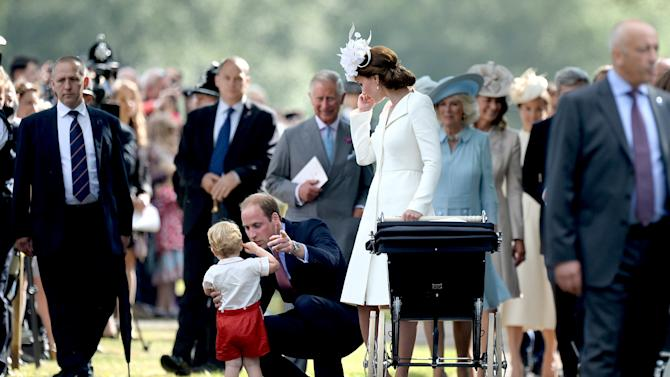 Britain's Prince William and Catherine, Duchess of Cambridge, look after their son Prince George as they walk past the crowds after the christening of their daughter Princess Charlotte, at the Church of St Mary Magdalene on the Sandringham Estate