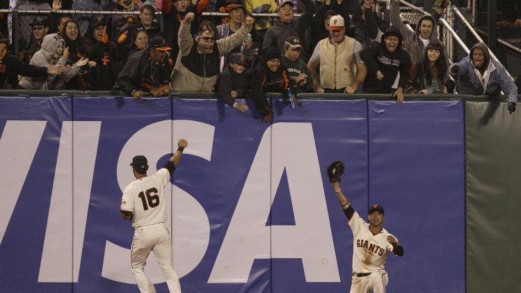 San Francisco Giants center fielder Gregor Blanco, right, celebrates with left fielder Angel Pagan (16) after catching a fly ball hit by Houston Astros' Jordan Schafer during the seventh inning of a baseball game in San Francisco, Wednesday, June 13, 2012. Giants pitcher Matt Cain pitched a perfect game. The Giants won 10-0. (AP Photo/Jeff Chiu)