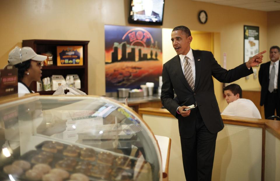President Barack Obama makes an order during unannounced visit to Krispy Kreme Doughnuts, Thursday, Oct. 25, 2012, in Tampa, Fla. Obama, who traveled to Florida for a campaign event nearby, surprised local patrons when he drove up in the morning. (AP Photo/Pablo Martinez Monsivais)