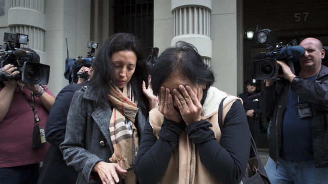 A mourner cries at a memorial outside the apartment building of the two children allegedly stabbed by their nanny, Friday, Oct. 26, 2012, in New York. The 2-year-old son and 6-year-old daughter of a CNBC executive were found dead by their mother in a dry bathtub in the family's Upper West Side apartment Thursday night, allegedly stabbed to death with a kitchen knife by their nanny, who slit her own throat and collapsed near the children, police said. (AP Photo/John Minchillo)