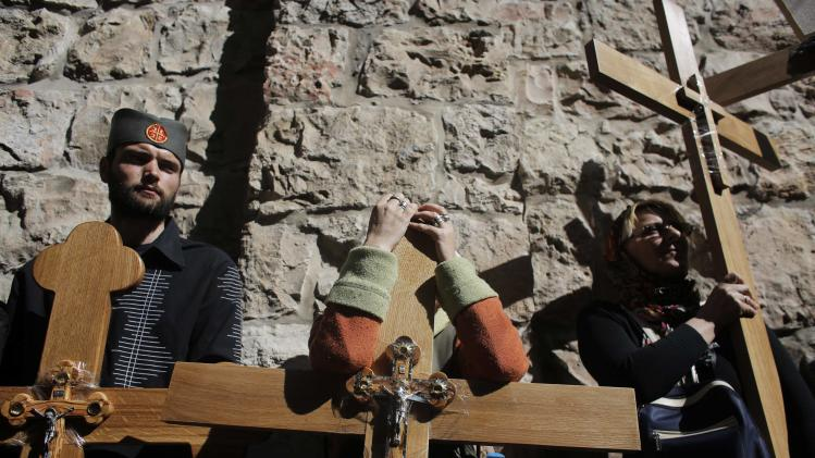 Christian worshippers hold crosses as they wait before the start of a procession along the Via Dolorosa on Good Friday in Jerusalem's Old City