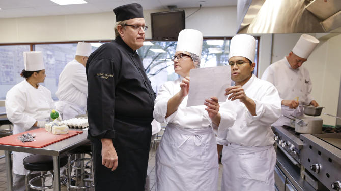 Chief instructor Larry Baumann, left, answers questions for students in a professional cook class at the Culinary Academy of Las Vegas, Friday, Dec. 14, 2012, in Las Vegas. The academy is funded through a trust created by the culinary and bartenders unions as well as management from 26 properties on the Las Vegas Strip. Nevada has become an increasingly Democratic state. And the Culinary Union's track record gives a dispirited labor movement some hope even as it continues to hemorrhage workers and reels from the signature of a right-to-work law in Michigan this week. (AP Photo/Julie Jacobson)