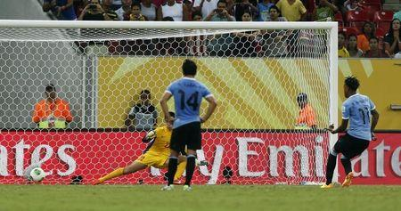 Uruguay's Abel Hernandez scores a penalty goal for his fourth, and his team's sixth goal against Tahiti during their Confederations Cup Group B soccer match at the Arena Pernambuco in Recife