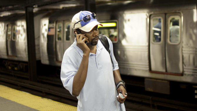 FILE - In this Sept. 27, 2011 photo, Mory Bailo Aw makes a cellphone call from a subway platform to get some last minute directions to a friends house in New York.  The biggest study ever to examine the possible connection between cellphones and cancer found no evidence of any link. The Danish study of more than 350,000 people concluded there was no difference in cancer rates between people who had a cellphone subscription and those who did not.  (AP Photo/Seth Wenig, File)
