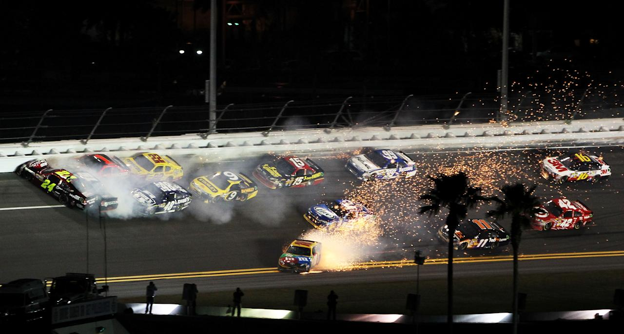 DAYTONA BEACH, FL - FEBRUARY 18:  Jeff Gordon, driver of the #24 Drive to End Hunger Chevrolet, and Kurt Busch, driver of the #51 Tag Heuer Avant-Garde Chevrolet Chevrolet, and Kyle Busch, driver of the #18 M&M's Brown Toyota, crash in front of the pack during the NASCAR Budweiser Shootout at Daytona International Speedway on February 18, 2012 in Daytona Beach, Florida.  (Photo by Jamie Squire/Getty Images)