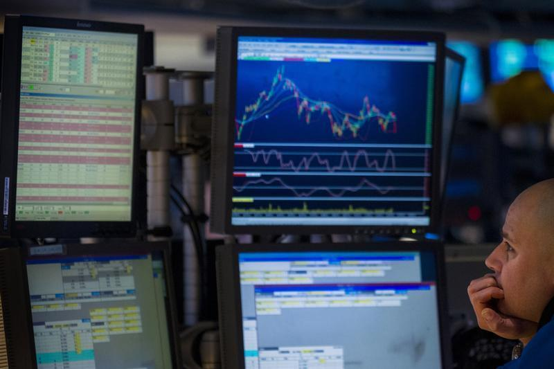 Trader watches multiple screens while at work on the floor of the New York Stock Exchange
