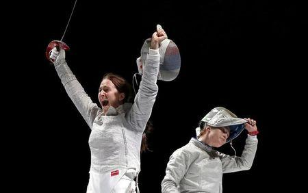 Russia's Sofya Velikaya (L) celebrates the victory over team Ukraine, with Ukraine's Olga Kharlan seen nearby, in their women's team sabre final at the World Fencing Championships in Moscow, Russia, July 17, 2015. REUTERS/Grigory Dukor