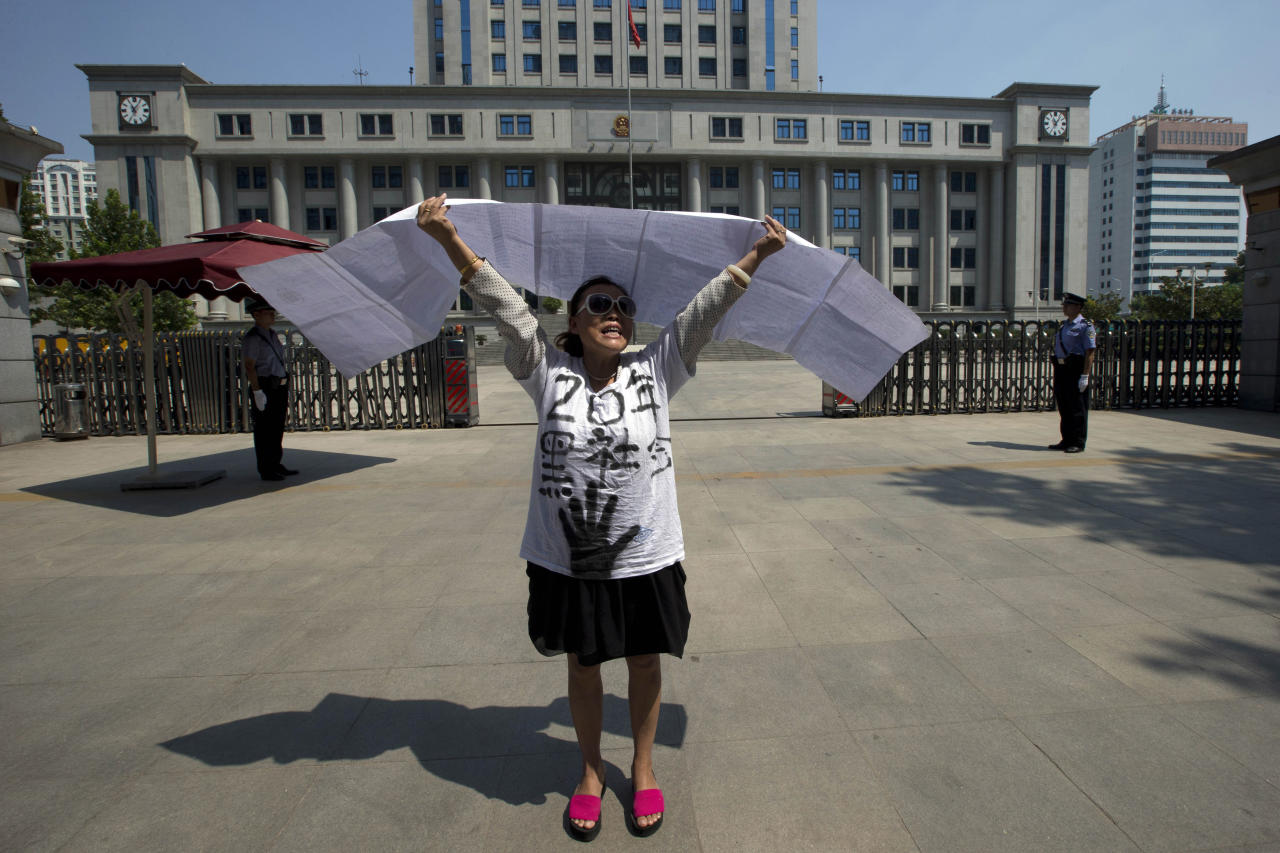 """A Chinese woman protests outside the Jinan Intermediate People's Court in Jinan, eastern China's Shandong province Wednesday, Aug. 21, 2013. Former Chinese politician Bo Xilai will stand trial at the court on Thursday on charges of corruption and abuse of power. Individual protestors have turned up at the court hoping to take advantage of media attention around Bo's trial to air their own grievances about China's legal system. The Chinese characters on her shirt reads """"20 years, Gangsters."""" (AP Photo/Ng Han Guan)"""