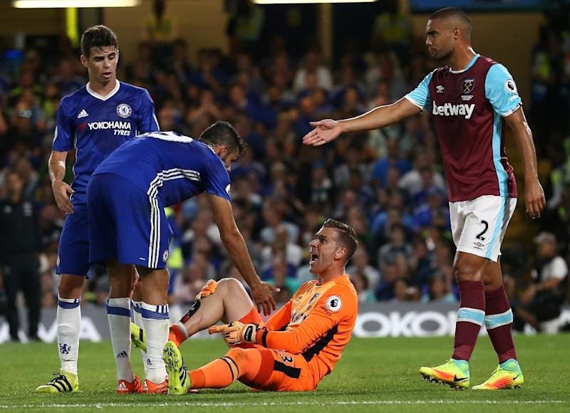 Chelsea's Diego Costa (2nd L) clashes with West Ham United's goalkeeper Adrian during their English Premier League match, at Stamford Bridge in London, on August 15, 2016