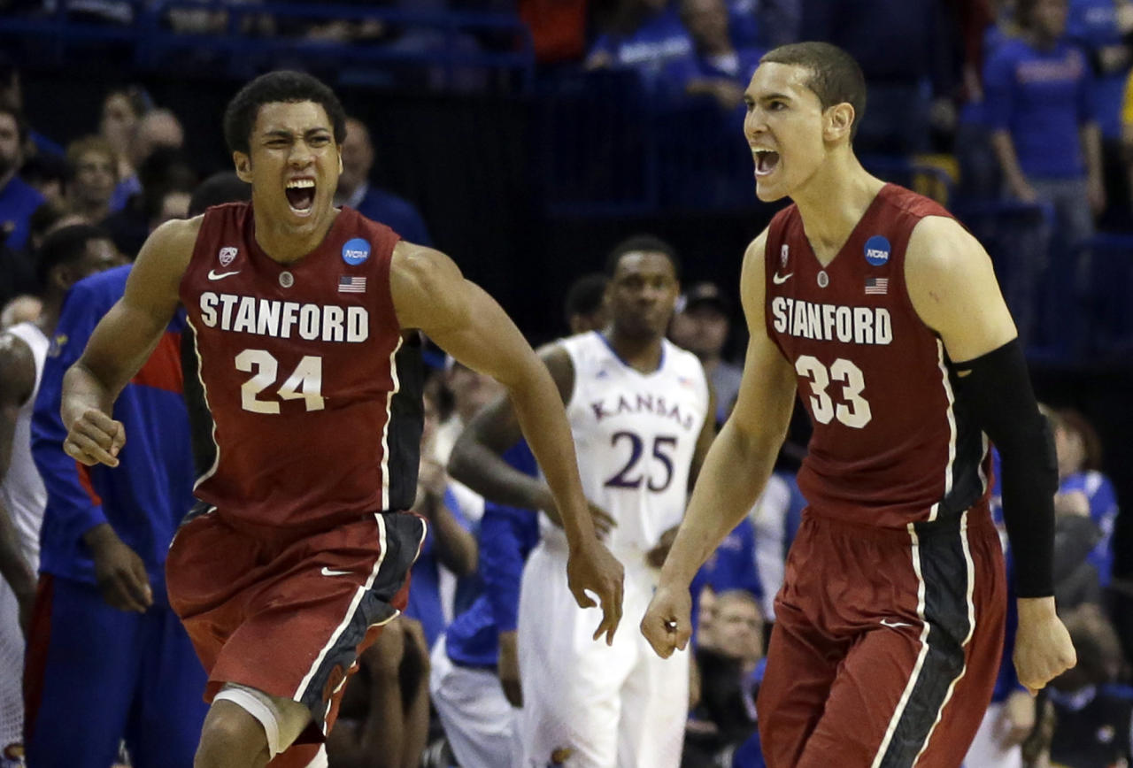 Stanford's Josh Huestis, left, and Dwight Powell, right, celebrate as Kansas' Tarik Black (25) watches in the background after in a third-round game of the NCAA college basketball tournament Sunday, March 23, 2014, in St. Louis. Stanford won 60-57. (AP Photo/Jeff Roberson)