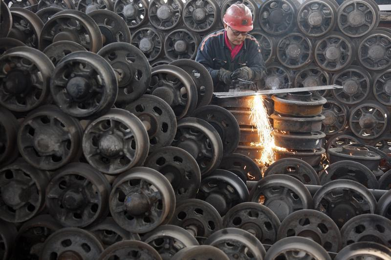 A worker welds a wheel for tramcar inside a factory in Huaibei