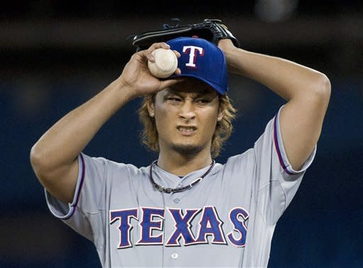 Texas Rangers starting pitcher Yu Darvish reacts while pitching against the Toronto Blue Jays during the second inning of a baseball game in Toronto on Monday, April 30, 2012. (AP Photo/The Canadian Press, Frank Gunn)