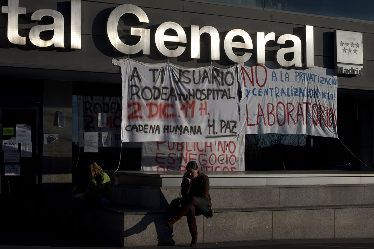 A woman makes a phone call outside La Paz hospital during a protest against cuts to the national health service in Madrid.
