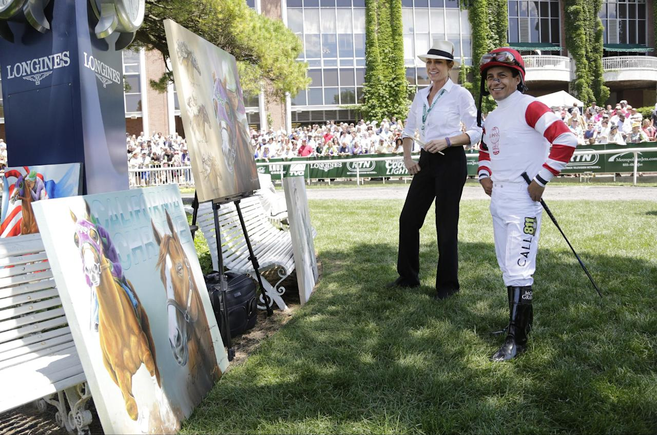 Jockey Victor Espinoza, right, looks over artwork by Susan Sommer-Luarca before riding in an undercard race at Belmont Park, Saturday, June 7, 2014, in Elmont, N.Y. Espinoza will ride favorite California Chrome in the Belmont Stakes later in the day. (AP Photo/Mark Lennihan)