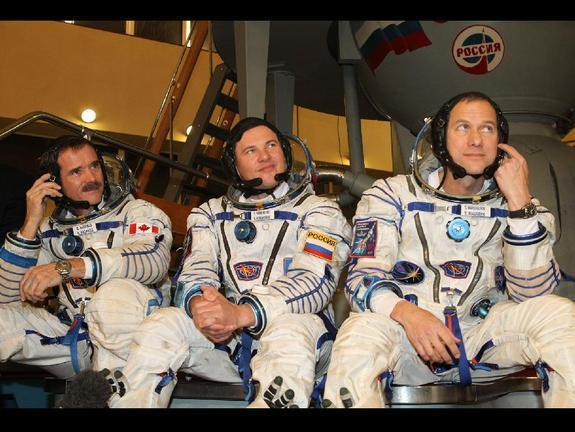 Expedition 34 Flight Engineer Chris Hadfield of the Canadian Space Agency (left), Soyuz Commander Roman Romanenko (center) and NASA Flight Engineer Tom Marshburn (right) are scheduled to dock with the International Space Station from the Soyuz