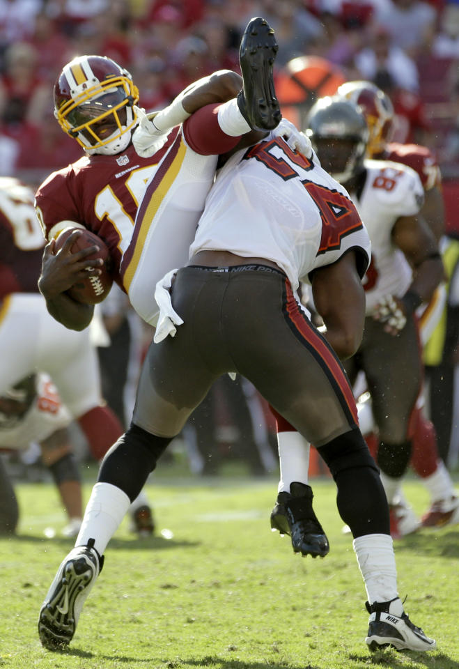 Washington Redskins quarterback Robert Griffin III (10) is upended by Tampa Bay Buccaneers strong safety Mark Barron (24) during the second quarter of an NFL football game Sunday, Sept. 30, 2012, in Tampa, Fla. (AP Photo/Margaret Bowles)