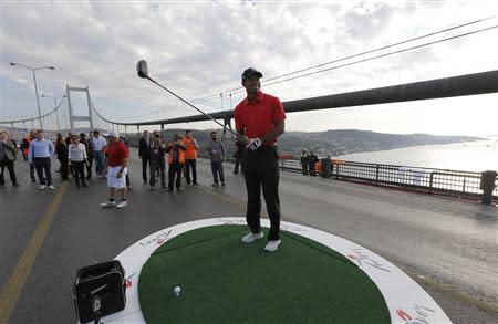 U.S. golfer Woods gets ready to hit a shot during an event to promote the upcoming Turkish Airlines Open golf tournament, on the Bosphorus Bridge that links the city's European and Asian sides, in Istanbul
