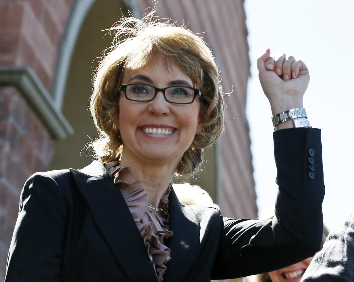 """FILE - In this Wednesday, March 6, 2013 file photo, former U.S. Rep. Gabrielle Giffords smiles as she raises a fist pump to the crowd as she, husband Mark Kelly, and a number of other Tucson mass shooting victims returned to the site of the shooting in Tucson, Ariz., that left her critically wounded to urge key senators to support expanded background checks for gun purchases. Giffords has been named this year's recipient of the John F. Kennedy Profile in Courage award. The JFK Library and Museum announced Friday that the Arizona Democrat is being honored for the """"political, personal, and physical courage she has demonstrated in her fearless public advocacy for policy reforms aimed at reducing gun violence."""" (AP Photo/Ross D. Franklin, File)"""