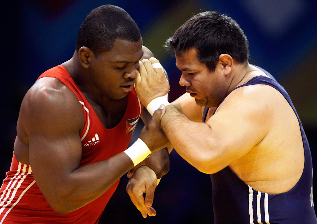 Mijain Lopez, of Cuba, left, fights with Rafel Barreno, of Venezuela, in a wrestling men's greco roman 120 kg final at the Pan American Games in Guadalajara, Mexico, Thursday, Oct. 20, 2011. Lopez won the gold medal.