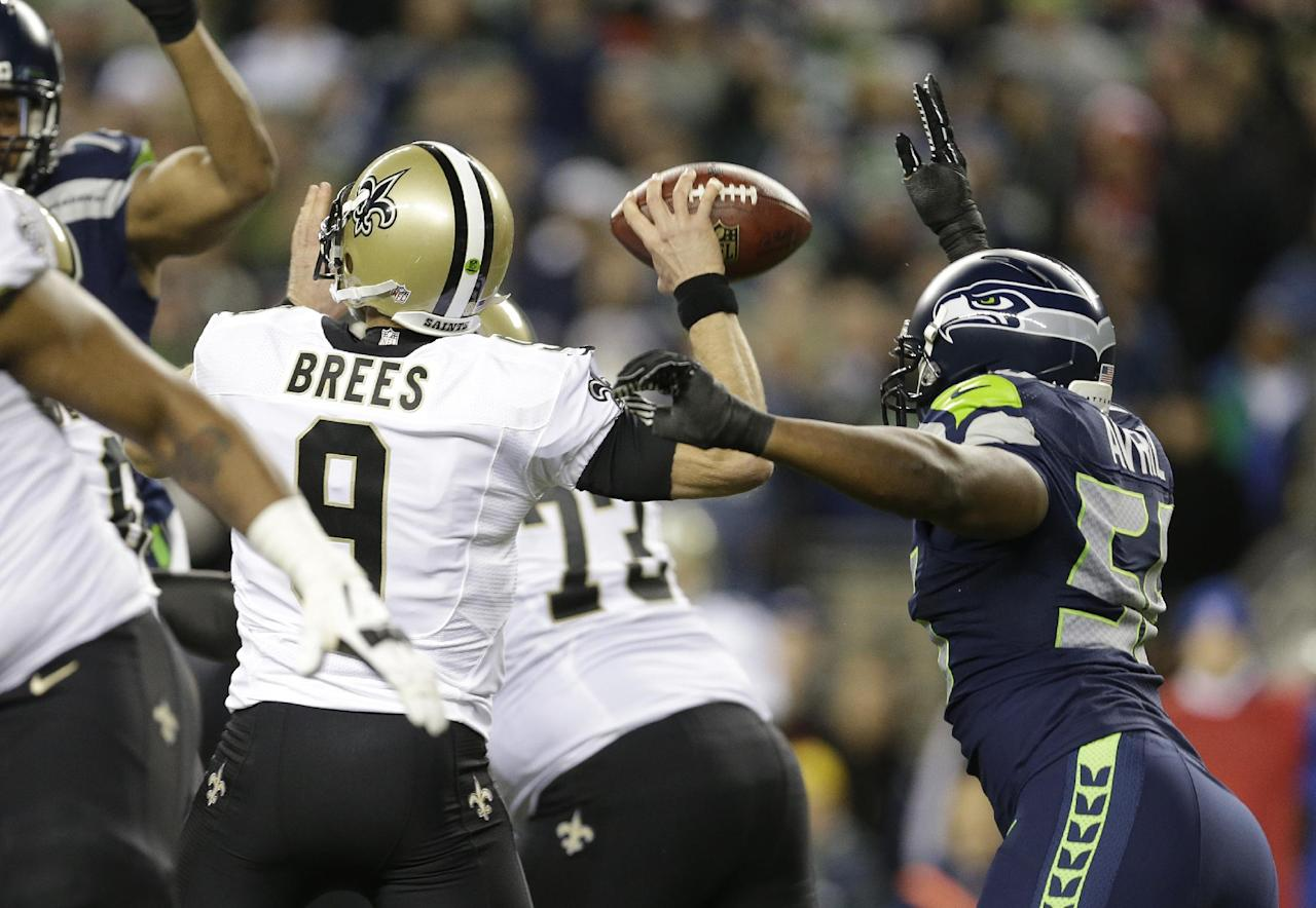 Seattle Seahawks defensive end Cliff Avril, right, causes New Orleans Saints quarterback Drew Brees (9) to fumble in the first half of an NFL football game, Monday, Dec. 2, 2013, in Seattle. Seahawks defensive end Michael Bennett recovered the fumble and ran for a touchdown. (AP Photo/Elaine Thompson)