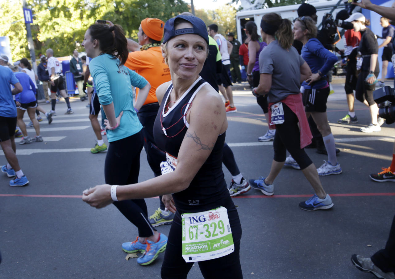 Actress Pamela Anderson smiles after crossing the finish line at the 2013 New York City Marathon in New York, Sunday, Nov. 3, 2013. (AP Photo/Seth Wenig)