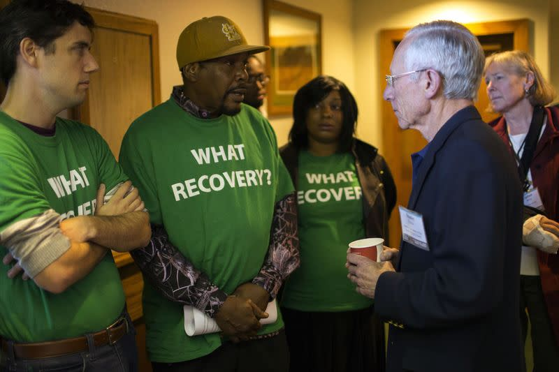 Fischer, vice chairman of the Federal Reserve System, speaks with a demonstrator at the Jackson Hole Economic Policy Symposium in Jackson Hole