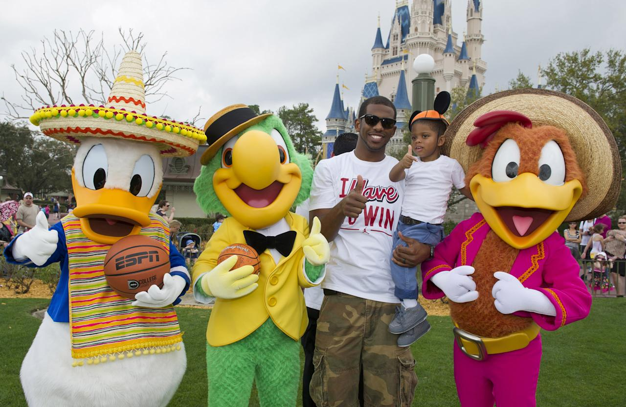 "LAKE BUENA VISTA, FL - FEBRUARY 23:  Los Angeles Clippers All-Star guard Chris Paul joins his son, Chris at the Magic Kingdom theme park at Walt Disney World Resort on February 23, 2012 in Lake Buena Vista, Florida.  Nicknamed ""CP3,"" Paul is posing with Disney's ""Three Caballeros"" in front of Cinderella Castle. Last night, Paul scored a season-high 36 points in the Clippers' 103-95 victory over the Denver Nuggets.  Paul, who also starred on Team USA's gold medal-winning squad at the 2008 Beijing Olympic Games, is in Orlando, Florida, for the NBA's 2012 All-Star Weekend.  He will be in the starting lineup for the Western Conference All-Stars during Sunday's NBA All-Star Game. The Clippers are 20-11 this season and are alone in first place in the NBA's Pacific Division. (Photo by Gene Duncan/Disney Parks via Getty Images)"
