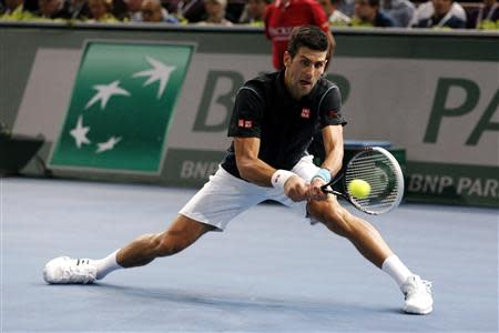 Djokovic hits a return to Ferrer in the men's singles final match at the Paris Masters men's singles tennis tournament in Paris