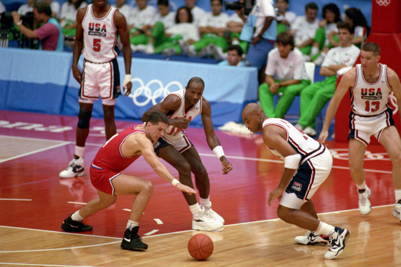 """BARCELONA, SPAIN - AUGUST 8:  Drazen Petrovic #4 of Croatia goes after the ball against Charles Barkley and Clyde Drexler of the United States in the 1992 Olympic game on August 8, 1992 in Barcelona, Spain. The """"Dream Team"""" defeated Croatia 117-85. NOTE TO USER: User expressly acknowledges and agress that, by downloading and or using this photograph, User is consenting to the terms and conditions of the Getty Images License Agreement. (Photo by Shaun Botterill/Getty Images)"""
