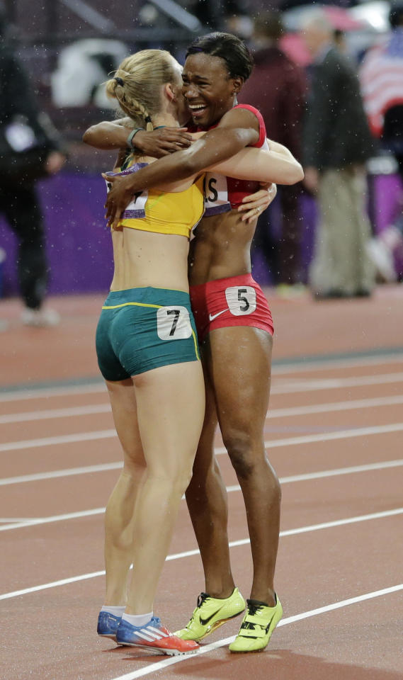 Australia's Sally Pearson, left, is embraced by bronze medallist Kellie Wells of the United States after she won gold in the women's 100-meter hurdles final during the athletics in the Olympic Stadium at the 2012 Summer Olympics, London, Tuesday, Aug. 7, 2012. (AP Photo/David J. Phillip )