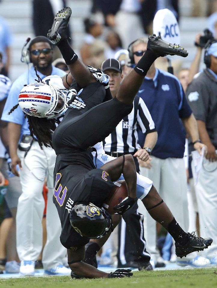 East Carolina's Lance Ray (3) is upended by North Carolina's Tre Boston following a pass reception in the first half of an NCAA college football game in Chapel Hill, N.C., Saturday, Sept. 28, 2013. (AP Photo/Gerry Broome)
