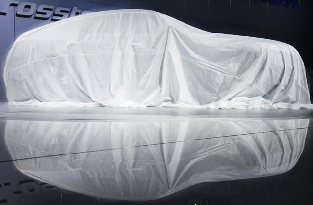 A shrouded 2013 Honda Crosstour is reflected in the showroom floor prior to its unveiling.