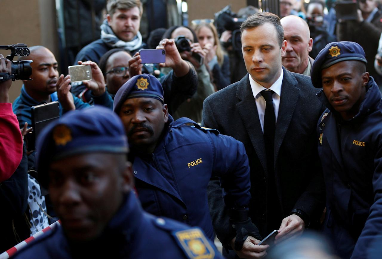 Paralympic gold medalist Oscar Pistorius is escorted by police officers as he arrives for his sentencing for the 2013 murder of his girlfriend Reeva Steenkamp, at Pretoria High Court, South Africa July 6, 2016. REUTERS/Siphiwe Sibeko/File Photo