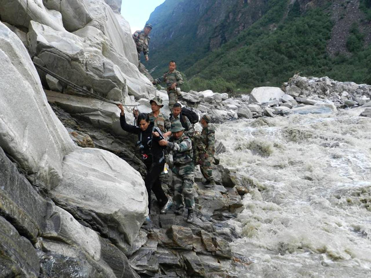 In this handout photograph received from the Ministry of Defence (MOD) on June 27, 2013, Indian defence personnel assist a stranded civilian to safety beside a raging river near the Pindari Glacier area of northern Uttarakhand state.  Rescue workers stepped up the search for bodies June 27 in India's flood ravaged north, as mass cremations of victims already discovered got underway amid fears of outbreaks of disease , officials and reports said.   AFP PHOTO / MOD
