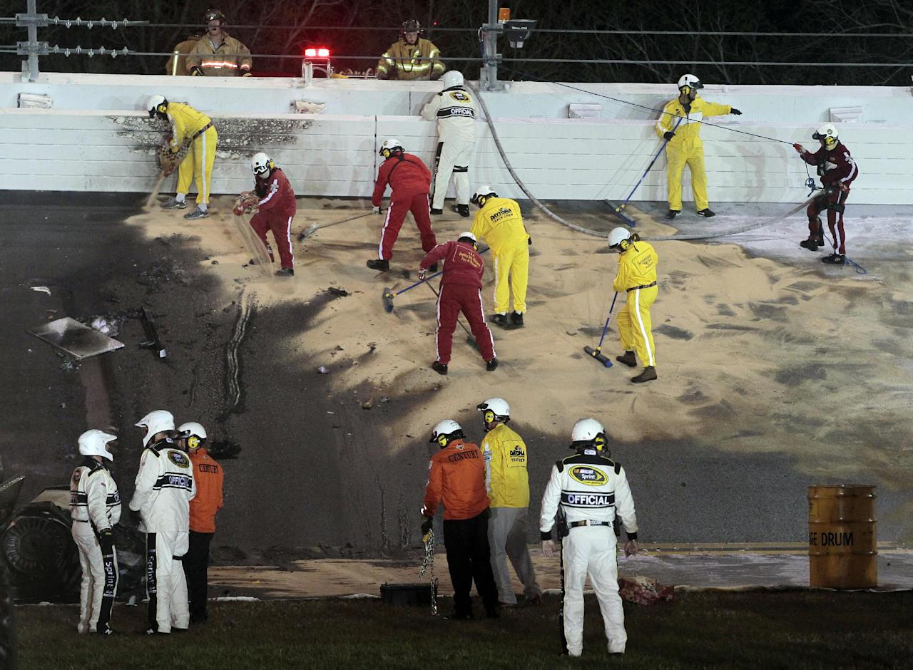 Workers clean up the track after Juan Pablo Montoya, of Colombia, crashed into a jet dryer during the NASCAR Daytona 500 auto race at Daytona International Speedway in Daytona Beach, Fla., Monday, Feb. 27, 2012. (AP Photo/Bill Friel)