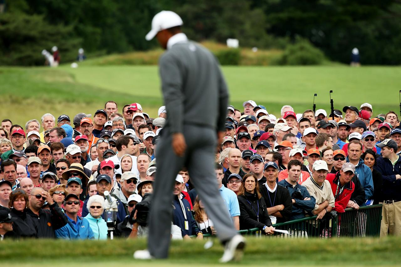 ARDMORE, PA - JUNE 14:  Tiger Woods of the United States walks across the 18th green as a gallery of patrons look on during a continuation of Round One of the 113th U.S. Open at Merion Golf Club on June 14, 2013 in Ardmore, Pennsylvania.  (Photo by Andrew Redington/Getty Images)