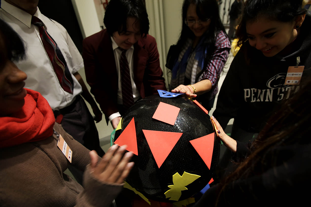 Students visiting the new National Museum of Mathematics put shapes on a three-dimensional surface.