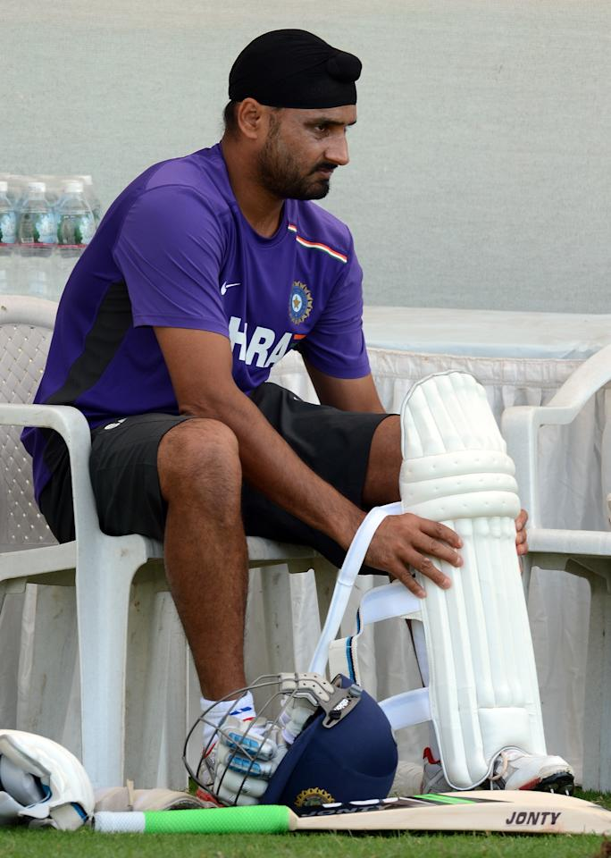 Indian cricketer Harbhajan Singh puts on his pads as he prepares to bat during a training session at The Sardar Patel Stadium at Motera in Ahmedabad on November 14, 2012. India plays their first test cricket match against England from November 15 in Ahmedabad. AFP PHOTO/ PUNIT PARANJPE