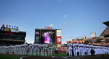 Braves and Phillies teams watch a military flyover during their opening day ceremonies at Turner Field in Atlanta.