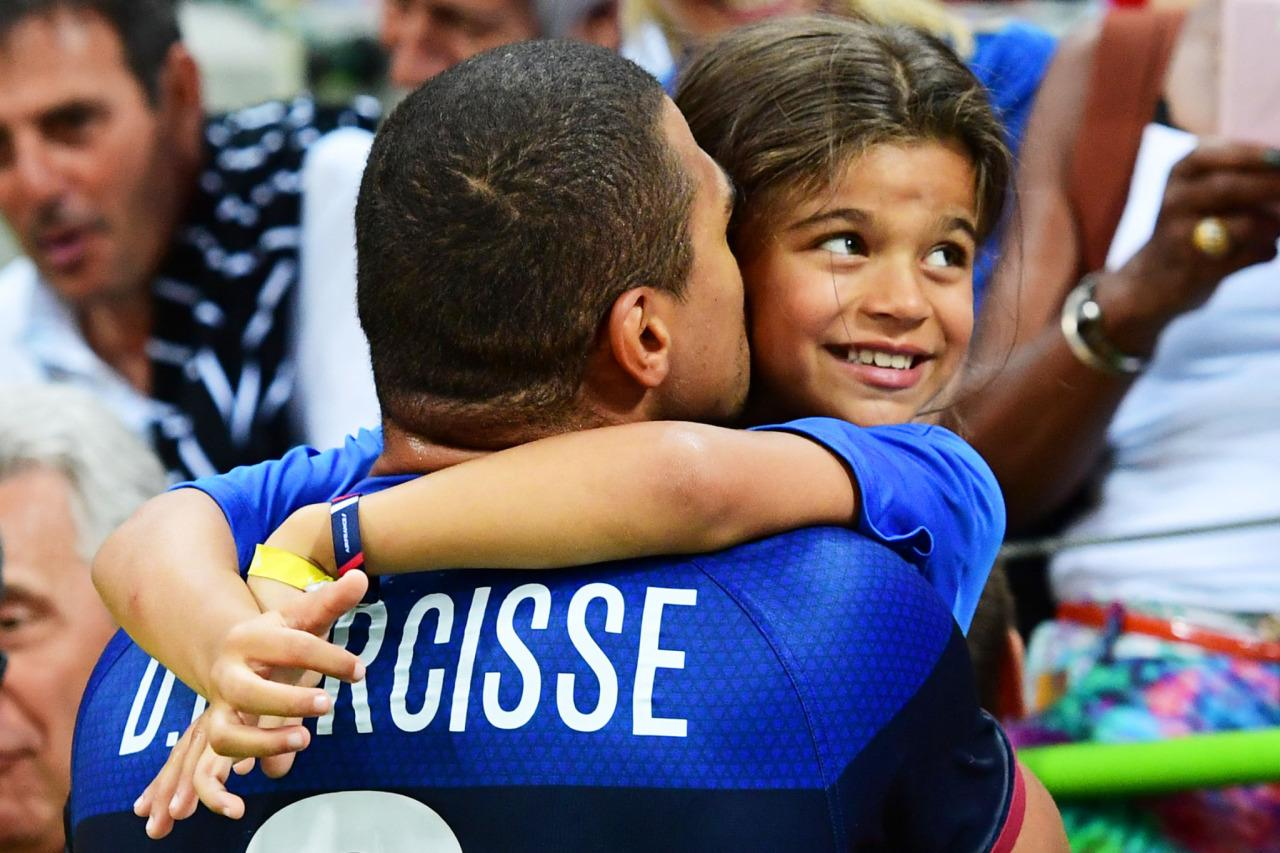 <p>France's Daniel Narcisse kisses daughter Aimy after the men's preliminary round handball match between Qatar and France.</p>