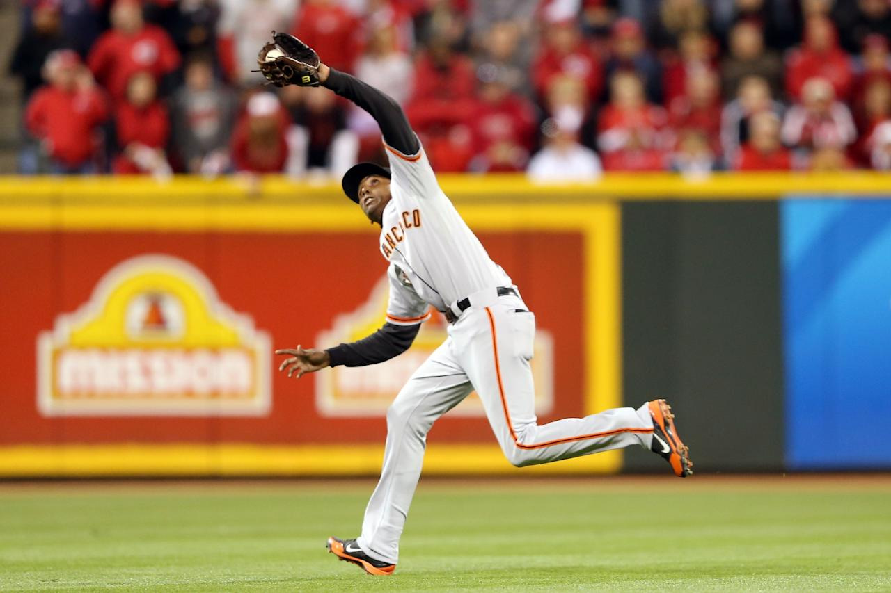 CINCINNATI, OH - OCTOBER 09:  Joaquin Arias #13 of the San Francisco Giants catches a fly ball by Jay Bruce #32 of the Cincinnati Reds in the eighth inning in Game Three of the National League Division Series at the Great American Ball Park on October 9, 2012 in Cincinnati, Ohio.  (Photo by Andy Lyons/Getty Images)