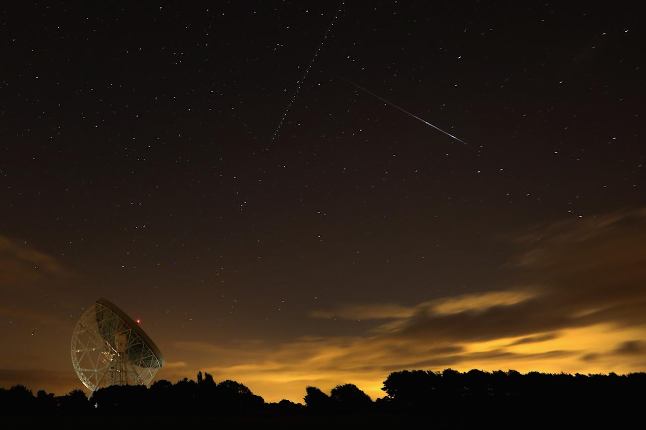 HOLMES CHAPEL, UNITED KINGDOM - AUGUST 13: A Perseid meteor streaks across the sky over the Lovell Radio Telescope at Jodrell Bank on August 13, 2013 in Holmes Chapel, United Kingdom.The annual display, known as the Perseid shower because the meteors appear to radiate from the constellation Perseus in the northeastern sky, is a result of Earth's orbit passing through debris from the comet Swift-Tuttle. (Photo by Christopher Furlong/Getty Images)