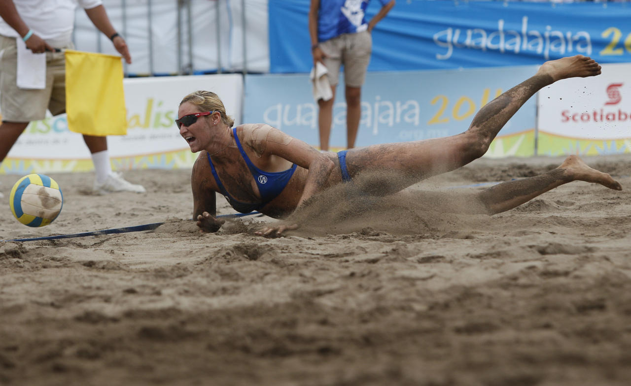 Heather Hughes, from the United States, falls during a women's beach volleyball match against Guatemala at the Pan American Games in Puerto Vallarta, Mexico, Monday, Oct. 17, 2011. (AP Photo/Ariana Cubillos)