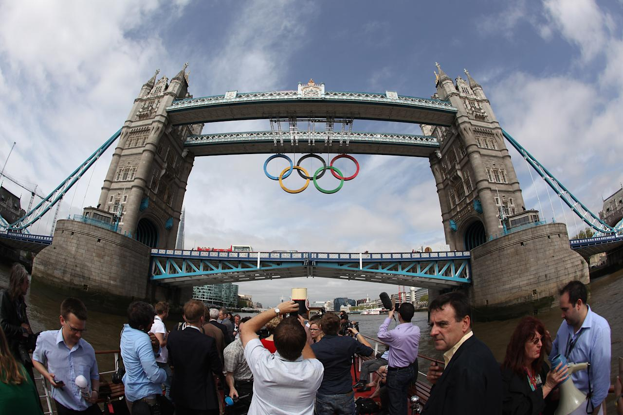 Members of the media work as a giant set of Olympic rings are displayed from Tower Bridge on June 27, 2012 in London, England. The rings weigh over three tonnes and measure over 25 metres wide by 11.5 metres tall; they will be illuminated in a light-show every evening during the Games.  (Photo by Oli Scarff/Getty Images)