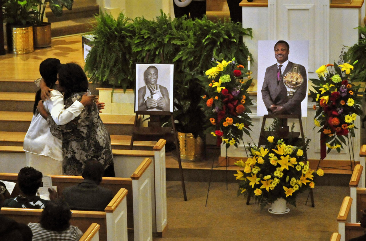 Joe Frazier's daughter Jacqui Frazier, left, and niece Dannette Frazier, right, hug during a memorial service for the former heavyweight boxing champion at the Bethesda Christian Fellowship Temple, Wednesday, Nov. 16, 2011 in St. Helena Island, S.C. Frazier died earlier this month from liver cancer. He was 67. (AP Photo/Stephen Morton)