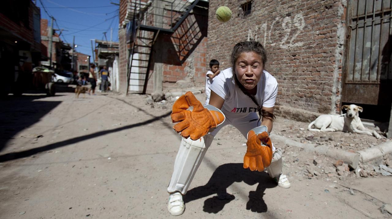 Caacupe cricket team member Milagros Mendez prepares to catch during a training session at the Villa 21-24 slum in Buenos Aires, Argentina, Saturday, March 22, 2014. The International Cricket Council has recognized the team, formed from the children of the Villa 21-24 shantytown, honoring them as a global example for expanding the sport, which in certain countries, like India, is widely played, but in many parts of the world restricted to elite sectors of society. Introducing cricket in the slum began in 2009 as an idea to transform the game into a social integration mechanism, before that it rarely breached the gates of the country's upscale private schools. (AP Photo/Natacha Pisarenko)